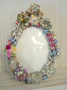 old pins and jewelry decorate a mirror frame