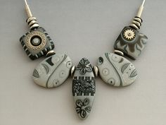 Black-n-Silver .............    Black and Silver mokume, accented with antiqued metal snap , vintage watch gear and silver nugget beads.