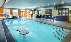 Indoor swimming pool with a bar, water slide, tv.