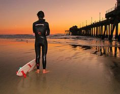 Surfer on the beach at sunset Orange County, California - Newport Beach Pier