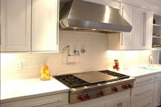 White Shaker kitchen with stainless steel hood
