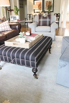 Striped ottoman / coffee table with brass tacks detail. casters. design indulgence