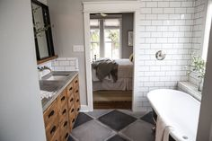 Two toned tile floors, subway tile and a black clawfoot tub made this master bathroom feel like a true modern farmhouse design.