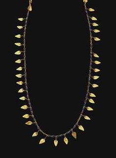 A ROMAN GOLD AND GLASS NECKLACE A ROMAN GOLD AND GLASS NECKLACE CIRCA 2ND-3RD CENTURY A.D. Composed of lengths of figure-8 loop-in-loop chain, interspersed with blue glass beads and leaf-shaped sheet pendants, with a hook-and-loop closure, each with a leaf-shaped sheet attached 17¾ in. (45.1 cm.) long