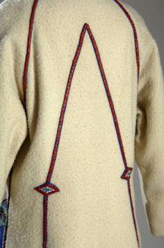 Coat (image 3 - detail) | House of Poiret | Paris | 1923 | Coat of white wool, with patch pockets of blue felt trimmed with red and silver leather and flowers of red and green. Coat buttons right over left; falls below the knee | Chicago History Museum | Object #: 1950.259