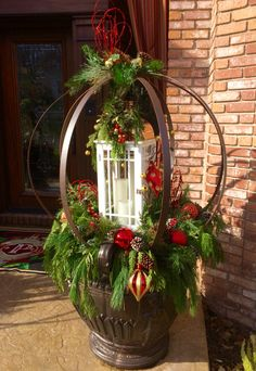 Front entry Christmas Urns with Lanterns. Decorating with iron spheres, fresh garland, Christmas ornaments and battery powered candles. The perfect decoration for the holiday season.