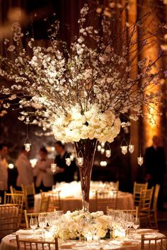 All-white flowers, branches, and hanging candles create a stunning winter centerpiece.
