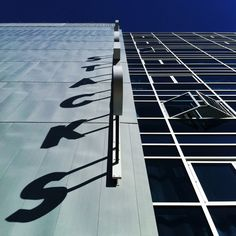 Bookmen Stacks residential building by architect James Dayton photographed by Minneapolis-based photographer Eric Mueller. It has a beautiful sign with the word STACKS that casts shadows across the facade in the afternoon. via passion passport