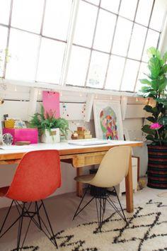 Sous une grande verrière, une simple table en bois, des objets en couleur et des plantes vertes. Le tout réchauffé par un tapis de laine.