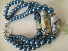 3-Strand Teal blue bracelet made w/teal blue beads, blue & white Lampwork beads, silver spacers & clasp. Lampwork beads have blues, browns, $55.00
