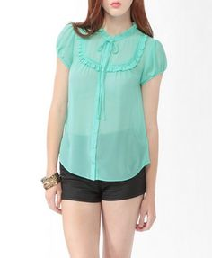 Sheer Ruffled Shirt A feminine shirt featuring a ruffled stand up collar and a self-tie bow. Nine button placket. Ruffled yoke with a lace inset detail. Lightly shirred back yoke. Short sleeves. Finished hemline. Sheer. Unlined. Woven. Lightweight.