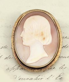 A 19th century shell cameo brooch, by Saulini  The oval cameo carved to depict the the profile head of a young girl, signed L. Saulini, for Luigi Saulini (1819-1883) the gold mount with engraved border, the reverse with maker's initials J.L, circa 1860