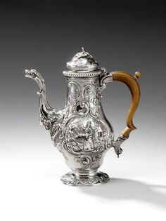 """A George II silver coffee pot, by Samuel Courtauld (I), London 1757, the pear-shaped body terminates in a spread circular foot chased with foliate scroll border, the body chased with """"C"""" scrolls, flowers and hatching and is applied with two plaques depicting oriental figures in landscapes, the curved spout with bird's head and bacchant mask, wood handle, the cartouche beneath spout is vacant"""