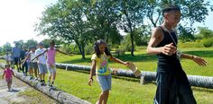 A group of kids walk along a wooden pole at Gateway National Recreation Area