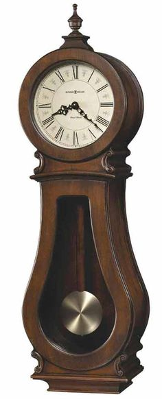 <p> This curvaceous wall clock features carved accents and a turned urn finial which complement the unique style. The aged dial offers black Roman numerals and decorative black hands. A special 80th Anniversary Edition. The wooden stick swinging pendulum features an antique-brass spun bob. Finished in Tuscany Cherry on select hardwoods and veneers. Quartz, dual chime movement%...