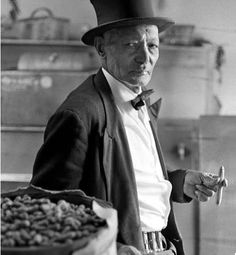 """""""Wanna-bag-o'-peanuts?"""" He'd sing out as one word, salted with a thick South Carolina accent. """"Peanut"""" Jim Shelton, with his trademark stovepipe hat and his tails, with a cart where he did his fresh-roasted peanuts. And he'd roast them and bag them for you, and you would take this warm bag of peanuts straight into Crosley Field. They were delicious! """"Peanut"""" Jim Shelton started selling hot roasted peanuts from a push cart in front of Redlands Field in 1932. He died in 1982 at the age of 93…"""
