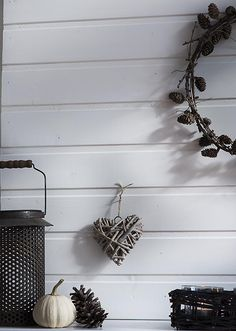 An easy, last minute mantel decoration for Fall with a pine cones wreath and lanterns. The background is a faux planked wall.  See the details at http://www.songbirdblog.com
