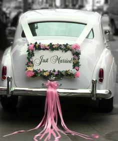 """Our 1962 white vintage Rolls Royce LWB wedding getaway car, with a """"Just Married"""" sign."""