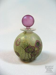 Isle of Wight Glass, 2001; Clear glass perfume bottle with surface-applied mottled gold leaf and pink glass floral pattern, frosted pink glass ball stopper
