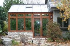 A greenhouse can function as a stylish adjoining room to your home where you can enjoy an indoor garden year round. The all mahogany frame, ridge cresting and stone walls of this design by Conservatory Craftsmen also includes in-floor heating.