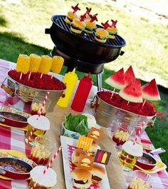 Backyard BBQ table - love the corn and watermelon on skewers in metal bins, and paper cupcake holders inverted over drinks to keep bugs out.  And the kraft paper/paper bag runner is cute!