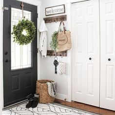 "Hello everyone! Wanted to quickly share a shot of our front entry way. We made only a few small changes here, but they made a huge impact. I painted the interior part of the door from white to Wrought Iron by #benjaminmoore (my fave interior door colour ) then we replaced all the 2"" orange oak trim with flat white trim, and then added these simple hooks behind the door for backpacks and bags, and that's it! This was a small budget friendly makeover that's made such a huge difference in her"