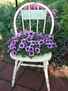 My chair,I cut a hole in the seat and painted it. I sealed with varnish. I added  flowers and a sign I made. I love it. It's also nice to use a mum in it in the fall.