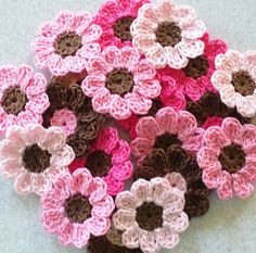 21 thread crochet flowers in pinks and brown. The pink flowers have Fudge Brown centers. 6 Hot Pink 6 French Rose 6 Orchid Pink 3 Fudge Brown with pink centers These are ready to add to scrapbooks, greeting cards, hair clips, clothes or crafts. Each flower is a little over 1 inch.