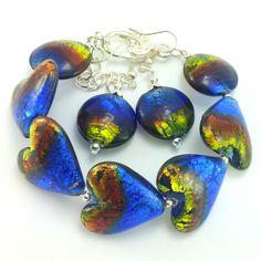 Komplet biżuteriidamskiej wykonany ręcznie. Kolczyki i bransoletkaz kolorowegoszkła weneckiego w odcieniu kobaltu, brązu i seledynu-oraz elementów w kolorze srebrnym. Koraliki w kształcie serc i dropsów.