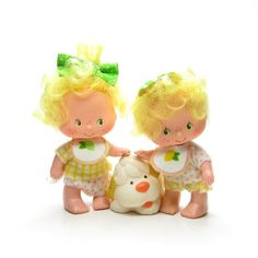 These vintage Strawberry Shortcake dolls are the twins Lem and Ada with their pet dog, Sugar Woofer. They're Strawberry Shortcake's International Friends and are baby characters, so they're smaller th