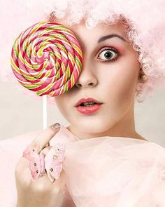 Girl with curly pink hair holding a multicolor swirl lollipop