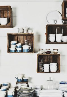 blue and white dishware and crate wall storage in kitchen