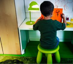 A boy sitting in front of STUVA bench with SKOJIG work lamp