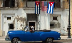 An old car passes by a house decorated with the flags of the United States and Cuba in Havana.