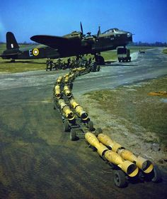 Sixteen 250 lb. bombs wait to be loaded on a Short Stirling bomber of No. 1651 Heavy Conversion Unit at Waterbeach, Cambridgeshire.  (Imperial War Museum Photograph.)