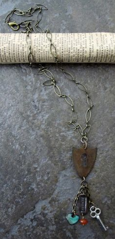 One of a kind handcrafted necklace featuring antique brass chain and findings, a vintage brass shield, a pewter key, copper charm and enameled heart charm.