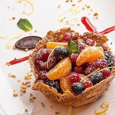 ensalada de frutas con frutos rojos en una cesta crujiente con limón menta y confeti avellanas picadas.