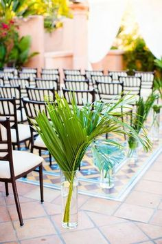 Aisle lined with large, tropical leaves in vases