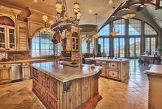 Mediterranean Kitchen with Kitchen island, limestone tile floors, Stone Tile, Breakfast bar, Chandelier, Raised panel, Flush