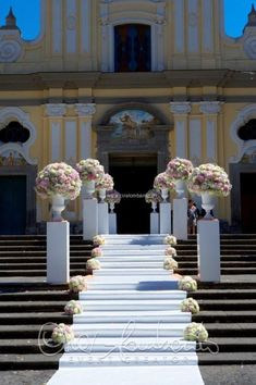 Romantiche composizione floreali incorniciano l'ingresso della chiesa di un matrimonio da sogno