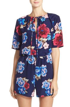 Vibrant blooms cover this swingy, warm-weather romper that boasts an adjustable tie neckline and comfy elastic waist.