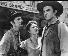 """Chester, Kitty & Marshall Dillon..... GUNSMOKE!  The first and most successful of the """"adult Westerns,"""" 'Gunsmoke' was a radio hit that was conceived as a TV show CBS hoped would star big-screen legend John Wayne. Wayne nixed the part, but recommended his pal James Arness, who would spend 20 seasons with Chester, Festus, Doc and Miss Kitty, playing Dodge City's pillar of law, order and Old West justice, Marshal Matt Dillon."""