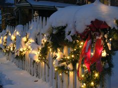 White Picket Christmas Fence with green garland & wreaths & red bows.
