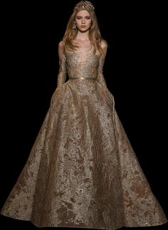 Gold long-sleeved gown, fully embroidered with silk threads and sequins, with a round neckline and a full skirt.