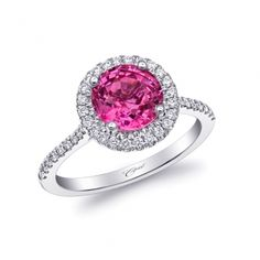 This 14K white gold ring boasts a vibrant 2.19CT round pink sapphire surrounded by a sparking diamond halo. Diamonds on the shoulders add an extra touch of sparkle. (LCK10046-PS) #CoastDiamond