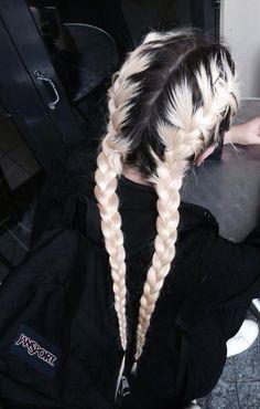 Dual black-rooted platinum blonde braids, long-sleeve black top, white shoes, & black JanSport pack; black-framed glass doors