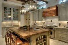 All of the elements create a European Rustic look with the beams, island, lanterns, copper hood and pot filler. Description from plush-design-studio.com. I searched for this on bing.com/images