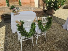 Garland with laurel for the chairs and satin gold vases with pink peonies, pale pink roses, white lisianthus, and greenery. Event Planner : Wedding Italy.