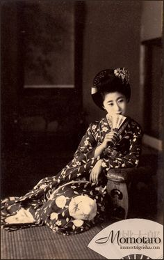 https://flic.kr/p/brBrq8   Maiko Momotaro with Insect Hikizuri   This particular hikizuri has always been one of my favourites to see Momotaro wear and I have many different postcards with her wearing it (she wore it for at least two separate photoshoots, with different han'eri and obi).    It wasn't until I received this postcard in my hands that I noticed that the circles on the hikizuri were filled with....insects!  I see what appears to be a praying mantis, cricket and fire fly.
