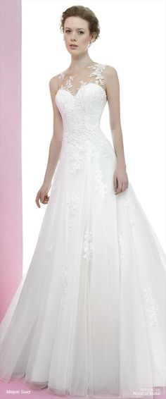 Wedding dress in embroidered tulle and lace. See though lace yoke with sweetheart neckline bodice. Voluminous embroidered tulle skirt and medium lenght tail.